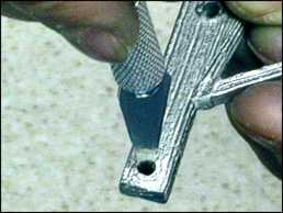 Use the knife to clean the connecting holes of any excess metal that affects the assembly.