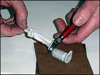 Carefully clip the metal ingot from the base of the figure.